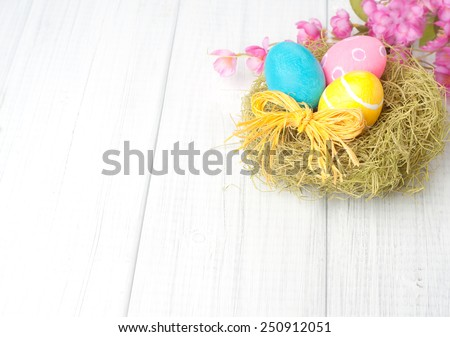 Pretty Easter Eggs in Nest with Pink Flowers in top corner of framework on Rustic White Wash Painted Used Boards with empty, blank room or space for copy, text, your words.  Horizontal Shabby Chic - stock photo