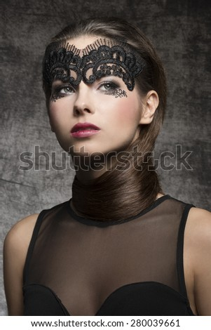 Pretty, elegant, stunning brunette woman with nice hairstyle covered her neck and mask on the face. she has hot nice nark makeup. She is wearing half transparent top. - stock photo