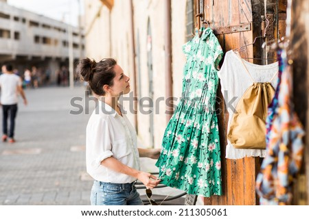Pretty elegant woman shopping in the vintage clothes store outside in old historical center in Jaffo in Israel. Moment of vocation or holiday. - stock photo