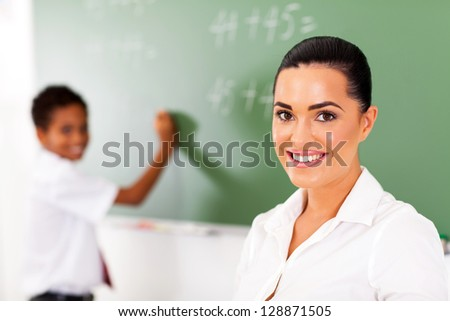 pretty elementary school teacher and student in front of chalkboard - stock photo