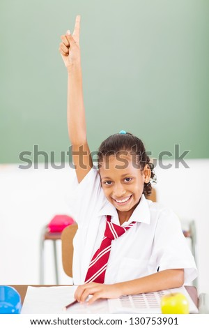 pretty elementary schoolgirl arm up in classroom - stock photo