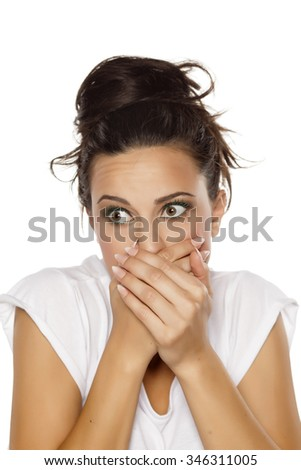 pretty embarrassed young woman covering her mouth with her hands - stock photo