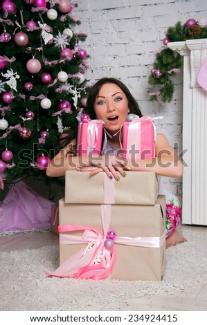 Pretty emotional brunette woman wearing an elegant white dress, sitting near a decorated Christmas tree and a fireplace, holding many presents, smiling, looking with surprise at camera. - stock photo