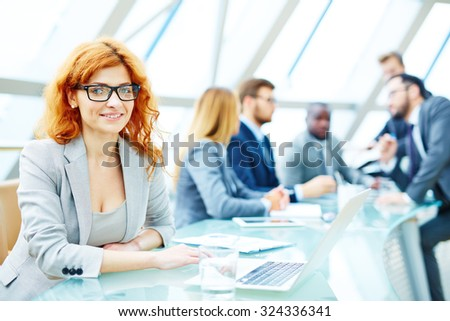 Pretty employee looking at camera in working environment - stock photo