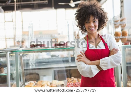 Pretty employee posing with arms crossed at the bakery - stock photo