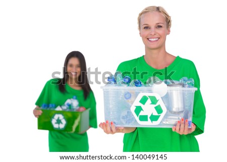 Pretty environmental activists holding box of recyclables and smiling on white background