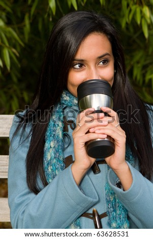 Pretty ethnic girl enjoying her coffee.