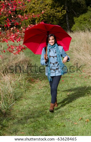 Pretty ethnic girl walking with a red umbrella.