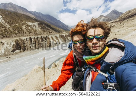 Pretty, european,couple climbing and hiking, the Tilicho Lake trail, in the Himalayas, Nepal.