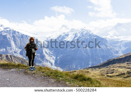Pretty, european, red-haired girl standing on the path in the mountains. Switzerland.