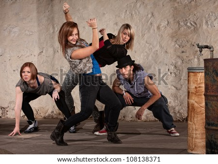 Pretty European woman dancing with Hip Hop group - stock photo