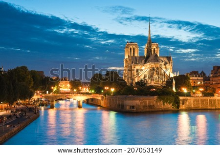 Pretty evening illuminations of the stunning Notre-Dame Cathedral (1163) and parisian apartments along the banks of the river Siene, Paris. - stock photo
