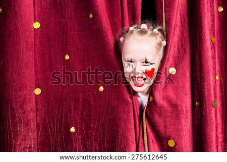 Pretty excited little blond girl on stage waiting to make her entrance on stage during a performance peeking out between the curtains and laughing - stock photo