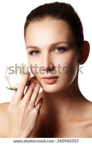Pretty face of beautiful young woman with rose on hands - white background. Beauty face of young woman with flower. Beauty treatment concept - stock photo