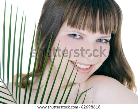 pretty face of woman hiding behind the big green palm leaf - stock photo