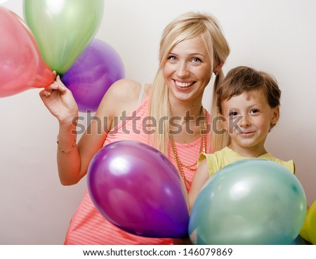 pretty family with color balloons on white background, blond woman with little boy on birthday party