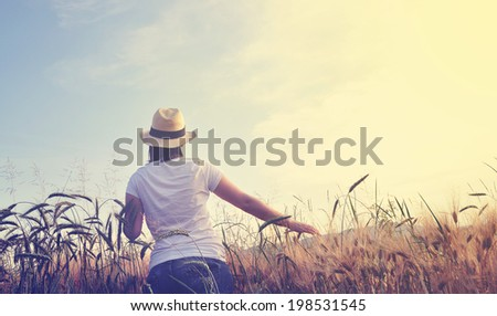 Pretty farm girl in the barley field looking at sunset in beautiful light, lifestyle vintage retro romantic look - stock photo