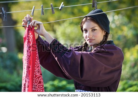 Pretty farmer girl hanging the laundry outdoors to dry - stock photo