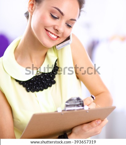 Pretty fashion designer working in office using mobile phone - stock photo