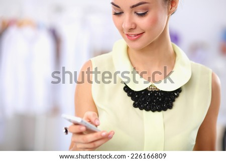 Pretty fashion designer working in office using mobile phone, isolated - stock photo