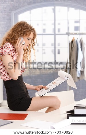 Pretty fashion designer working in office using mobile phone, sittin on table.? - stock photo