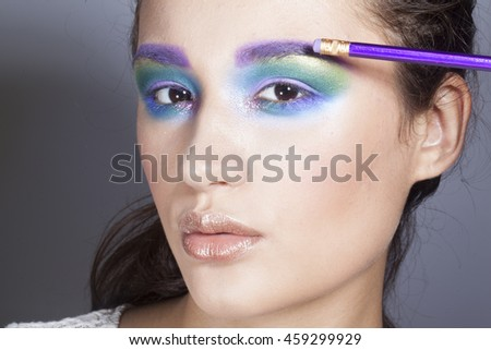 pretty fashion model girl with colorful make up with eraser next to eye