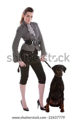 Pretty fashionable woman letting her doberman pincher out - stock photo