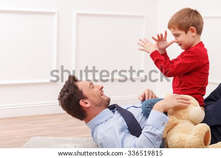 Pretty father and son are playing with joy. The parent is lying on flooring and holding his child with Teddy bear. The boy is gesturing near his face. They are smiling