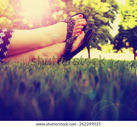 pretty feet on grass at sunset with nails painted and sandals on toned with a retro vintage instagram filter  - stock photo