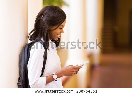 pretty female afro american university student using cell phone - stock photo