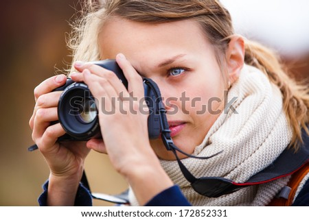 Pretty female amateur photographer taking photos outdoors, doing what she loves to do - stock photo