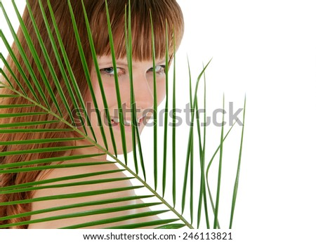 Pretty female behind palm leaf over white - stock photo