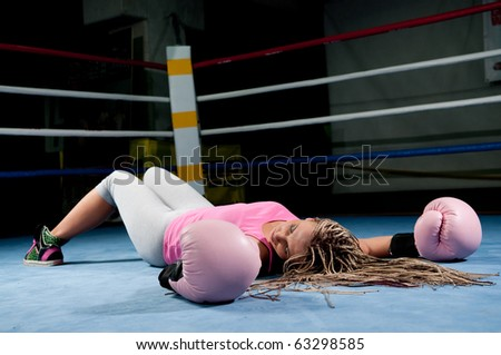 Pretty female boxer knocked out laying on the floor - stock photo