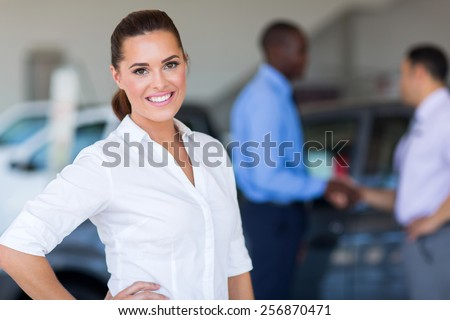 pretty female car dealer inside showroom - stock photo