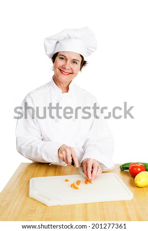 Pretty female chef chopping up vegetables in her kitchen.  Isolated on white.   - stock photo