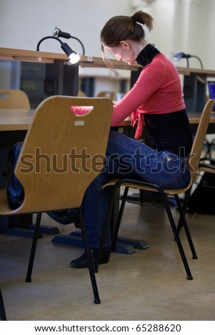 pretty female college student in a college library (shallow DOF; color tuned image) - stock photo