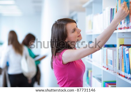 pretty, female college student in a library (shallow DOF; color toned image) - stock photo