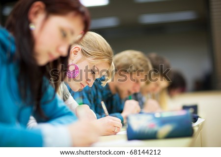 pretty female college student sitting an exam in a classroom full of students (shallow DOF; color toned image) - stock photo