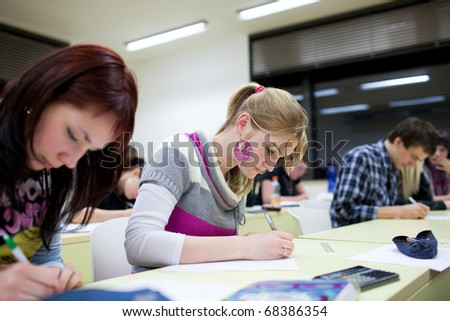 pretty female college student sitting in a classroom full of students during class (shallow DOF; color toned image) - stock photo