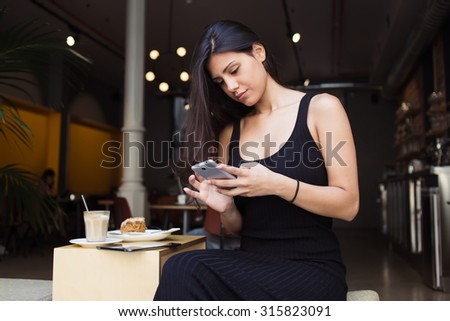 Pretty female connecting to wireless on telephone while resting in cozy coffee shop in the fresh air,attractive woman typing message on mobile phone while sitting in cafe terrace during lunch break - stock photo