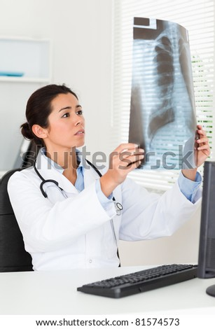 Pretty female doctor looking at a x-ray in her office