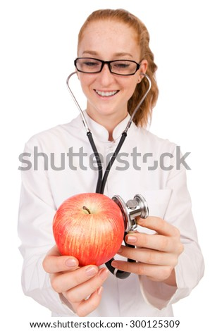 Pretty female doctor with stethoscope and apple isolated on white - stock photo