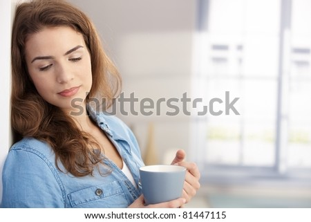 Pretty female drinking tea at home, daydreaming. - stock photo