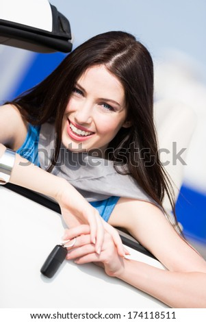 Pretty female driver in a car showing the car key - stock photo