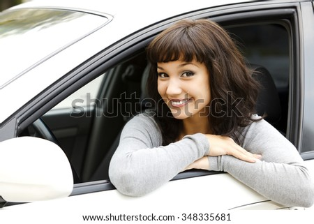 Pretty female driver in a white car