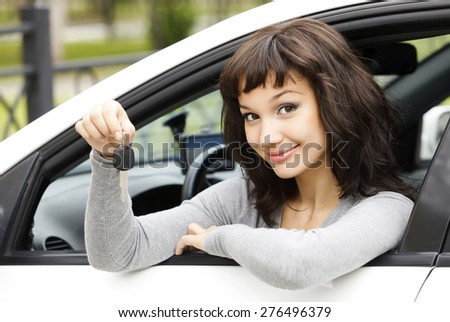 Pretty female driver in a white car showing the car key - stock photo