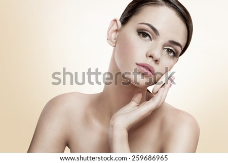 Pretty female enjoy a flawless skin, skin care concept / photoset of attractive brunette girl on light-brown background   - stock photo