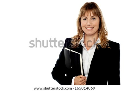 Pretty female executive holding notebook - stock photo