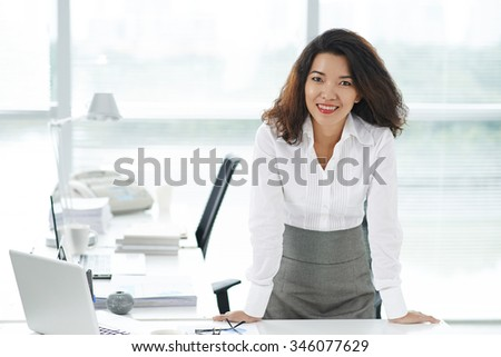 Pretty female executive standing at her table and smiling at camera - stock photo