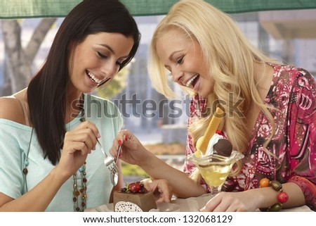 Pretty female friends sharing a chocolate cake at outdoor cafe, smiling happy. - stock photo